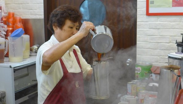 Surrounded by a cloud of steam, a Ya Kun worker makes coffee the traditional way